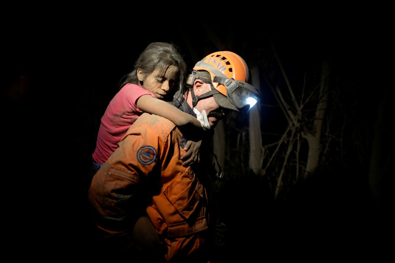 A rescue worker carries a child covered with ash after Fuego volcano erupted violently in El Rodeo